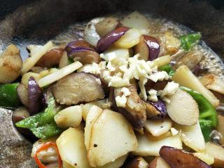 地三鲜--家常少油版,放入蒜末。再根据口味放适量的盐。翻炒至汤汁变稠。
