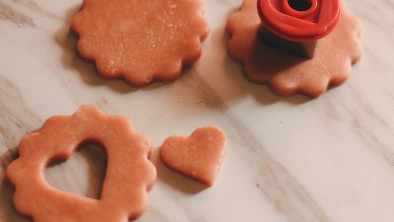 """草莓酱夹""""心""""饼干,用心型模具在其中一半的饼干胚上抠出心形图案。"""
