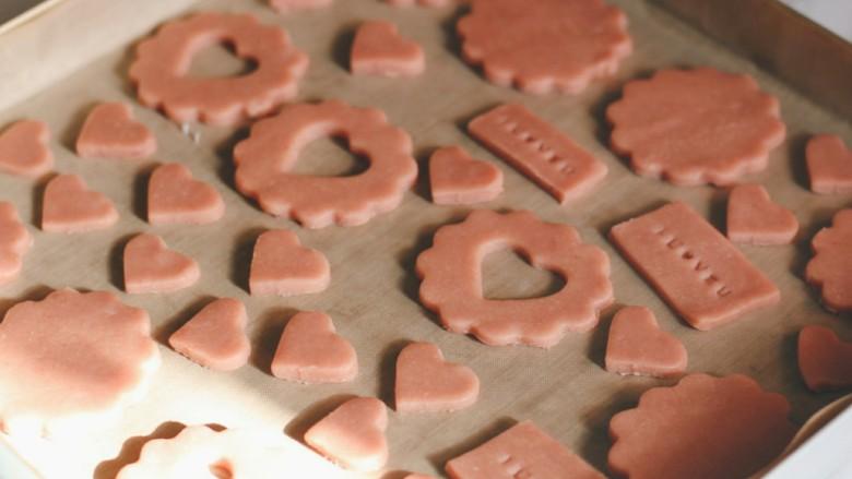 """草莓酱夹""""心""""饼干,所有面团全部压好模,放入烤盘中。 170度上下火,中层烘烤15分钟。"""