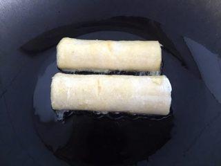 懒人料理-香蕉派,锅中放入适量的油,粘好鸡蛋液的卷放入锅中。