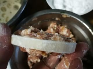 藕饼,藕片两面拍上一层生粉后,接着就放拌好的肉糜,用手取适量肉糜平整地轻轻按压在藕片一面的两边,很容易就粘住了,不用担心会掉。一面粘好肉糜再反过来粘另一面。(两手操作拍照片确实有点难度,只能文字陈述多一点😓)