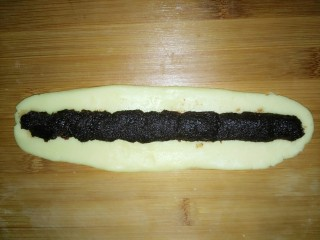 一口酥,擀扁成牛舌状 在正中间加入适量红豆沙馅 封口卷起
