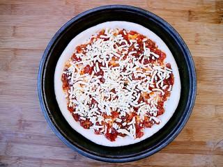 培根口蘑芝香披萨,在披萨酱上铺一层芝士碎。