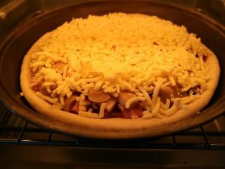 培根口蘑芝香披萨,预热烤箱后,把披萨饼放入烤箱中层,上下火150℃,烤大约25分钟。
