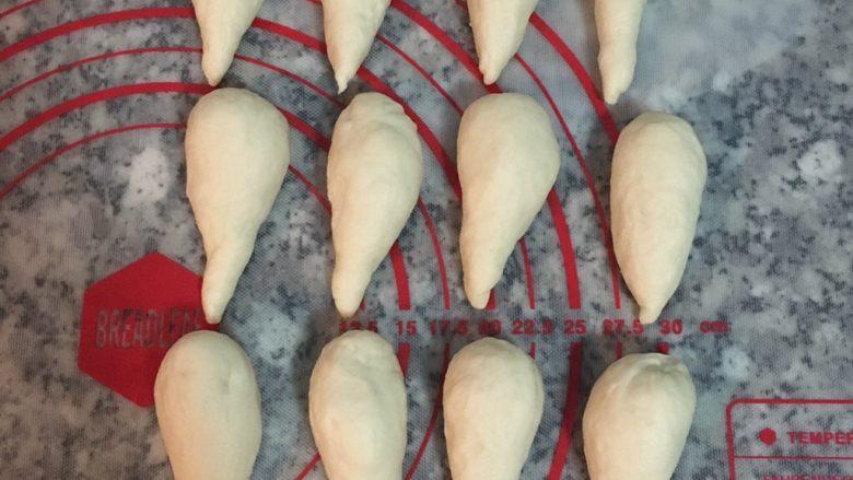 最爱面包+ 烟熏起司面包卷,取出面团略微整型后,秤重并进行分割,此原料可分成@20~22g x 24颗!!! 分好份量后,先滚圆再滚成水滴状,并照顺序排列好, 完成后盖上保鲜膜或拧干的湿布3分钟,让面团松弛一下.