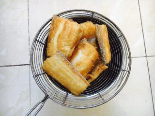 红烧带鱼,煎好的鱼放在笊篱里沥油。