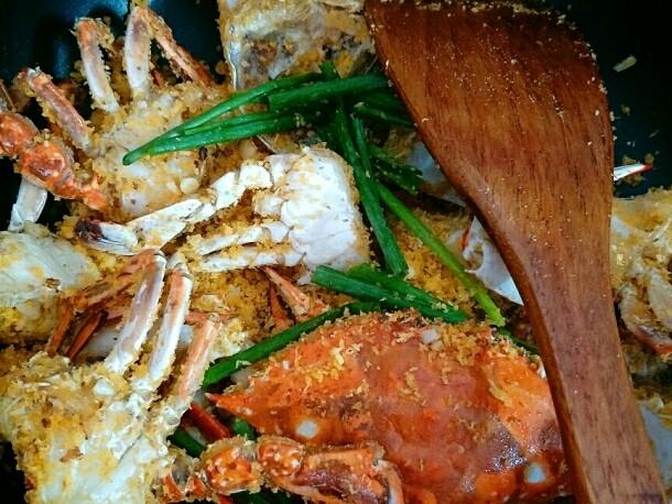 避风塘炒蟹,加入葱段炒至面包糠、蒜末裹在蟹块上为止