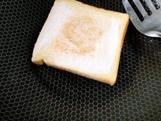 懒人料理+快手早餐,锅里放少许油,放入一片土司,小火慢煎,煎至底面有点焦黄把它翻个面。
