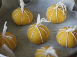 金灿灿的南瓜馒头,全部绑好后,放在温暖处二次发酵。