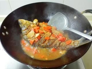 糖醋胡萝卜鳊鱼,调大火收汁,用锅铲把汤汁往鱼身上浇一浇