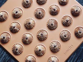 巧克力双色曲奇,裱花袋垂直均匀用力挤在阳晨马卡龙烤盘里,上面放一颗耐烘焙巧克力豆。