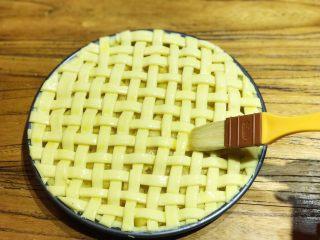 披萨模具也能做的酥皮苹果派,此时可预热烤箱,上下火200度15min。在编织好的派皮上刷上一层蛋液