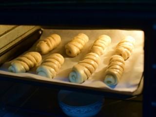 椰蓉小面包,放进烤箱进行二次发酵30分钟。烤箱中放一碗热水