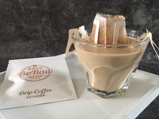 奶萃挂耳咖啡,一只手固定其中一只挂耳,另外一只手轻轻反复提放挂耳袋,使牛奶均匀浸润挂耳袋中的咖啡粉。