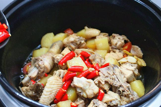 香辣土豆烧鸡,烹调时间结束,珐琅电炖锅发出嘀嘀的提示声,这时汤汁略干,倒入辣椒拌匀,铲起或整锅端出食用。