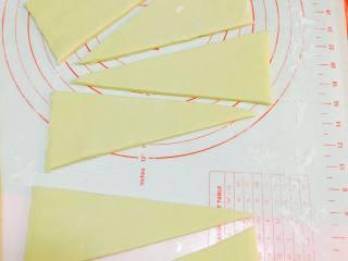 法式可颂,从冰箱取出。将面片擀成厚度4毫米厚长方形片。分割成等腰三角形。
