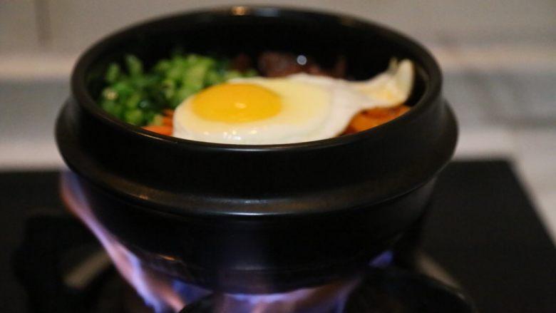 腊肠石锅拌饭,放上炒好的香菇/腊肠/青菜/胡萝卜和准备好的韩式辣萝卜,放在炉子上小火加热至米饭四周出现焦黄香气即可。