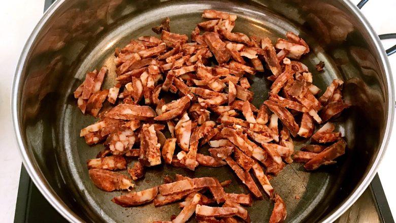 腊肠煲仔饭,炒锅烧热后加入腊肠丝