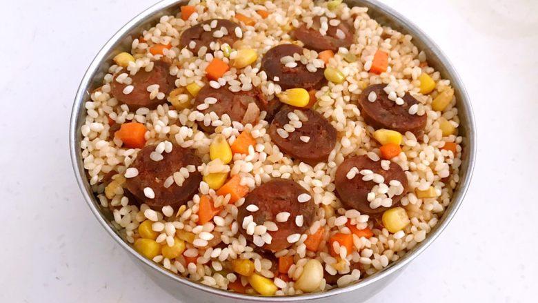 腊肠煲仔饭,把炒好的腊肠糯米放入容易导热的不透刚盆中