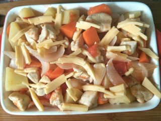 西红柿鸡肉焗饭,铺上炒好的番茄鸡肉,撒适量芝士