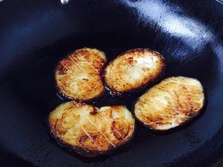 #圆土豆# 土豆烧茄子,起锅锅热放入50g的油,中火,放入茄子片,每片每面煎制约2分钟左右,把茄子的两面都煎至金黄色。煎好的茄子,沥一下油。