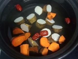 山药、胡萝卜大米粥,砂锅中放入适量水,放入胡萝卜、山药、红枣。