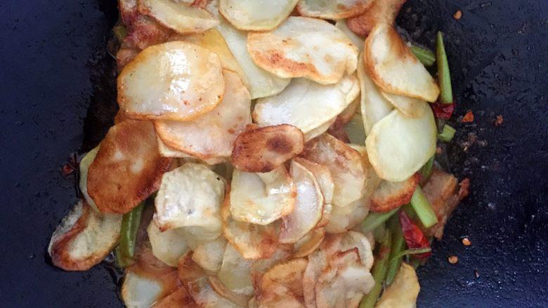 干锅土豆片,炒好的底料倒进干锅里,没有干锅的直接在炒锅里也可以,土豆片铺在上面然后小火慢慢煎
