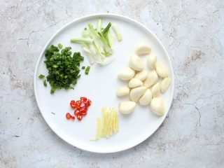 蒜香鲳鱼,蒜剥用刀背拍扁,去蒜衣;姜去皮切丝;葱白切段,葱绿切葱花;小米辣切小圈。