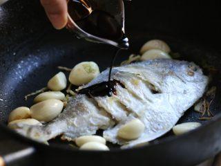 蒜香鲳鱼,再次放入鲳鱼,调入红烧酱油一汤匙、黄酒一汤匙。