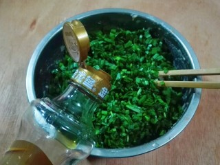 真的很满足~麻油韭菜大馄饨,韭菜洗净切碎放进小盆子里,放少许麻油拌匀