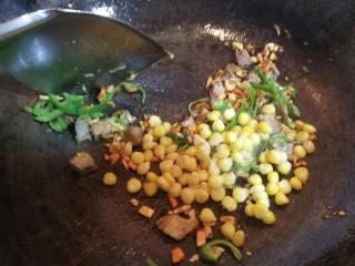 爆炒藕粒青椒肉,接着放入玉米粒儿,轻炒几下。