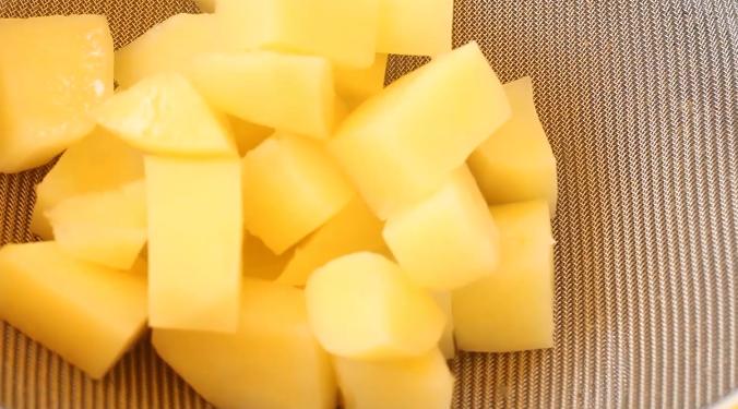 土豆芝士球,将煮熟的土豆块捞出,放在过滤筛里,虑去多余的水分。