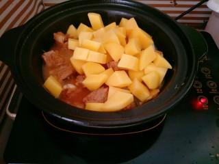 土豆烧排骨,下入土豆块煮透,加少许盐、味精调味