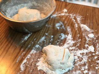 蛋葱油饼,桌子上将放点面粉、将一块面团放在桌子上(注意:这个面团有点黏,需要在面团下上、手上加面粉).