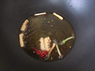 酒酿红烧鸡,放入姜片、葱白和辣椒段爆香
