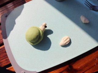 乌龟馒头,分别取四个白色的水滴状小面团,压扁用刀叉压出痕迹,放乌龟的壳下面做乌龟的脚