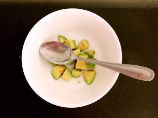 三文鱼牛油果沙拉,把牛油果切成1㎝左右见方的小块,加入半勺柠檬汁调匀