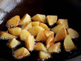 『土豆茄子煲』,锅内倒入色拉油,油热后倒入土豆炸至金黄色