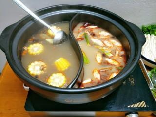 鸳鸯火锅,水开后,清汤那边加入玉米、红枣,辣汤这边加入姜片、大葱