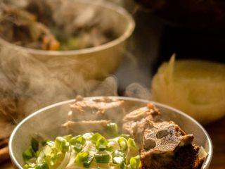 羊蝎子红汤面,把肉放入面上,撒上葱花