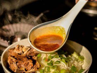 羊蝎子红汤面,把热汤浇到面上。