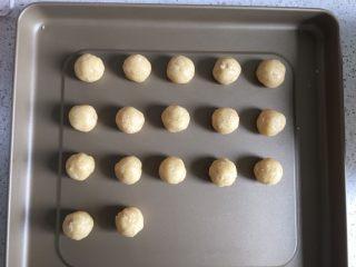 花生小小酥,把面团分为15g一个的小面团,揉圆放入烤盘