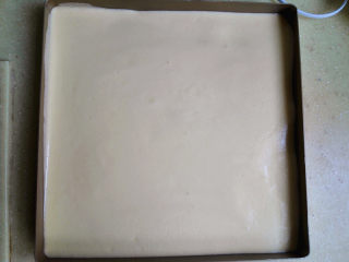 盒子蛋糕,倒入不粘烤盘里,表面刮平,再震出大气泡,如果烤盘不是不粘的,则要铺油纸或是油布防粘,