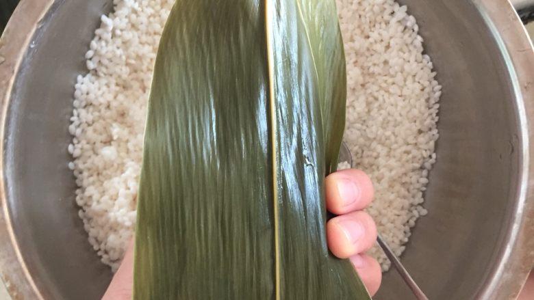 肉粽子,重点来了,把后面的叶子盖过来顺势用手压住右边的叶子