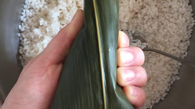 肉粽子,另一只手辅助,把左边的叶子也压下来