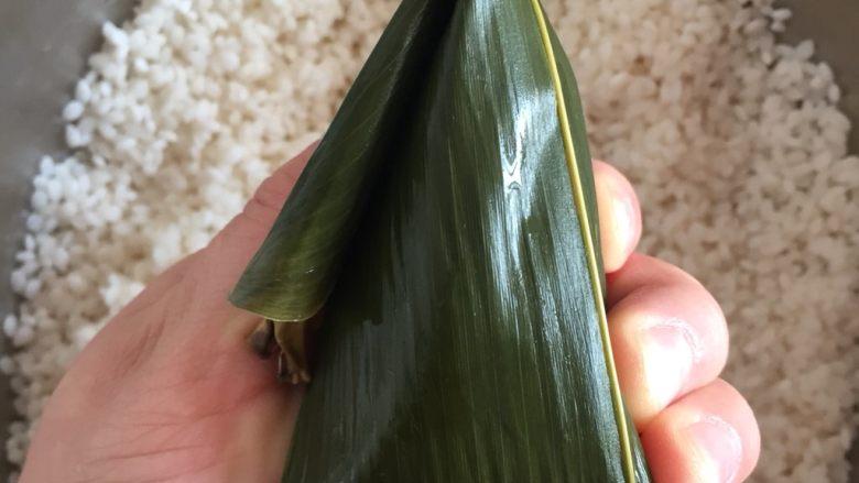 肉粽子,把前面多余的长出来的叶柄折过来,这样一个粽子就包好了,拿过来事先准备好的棉线