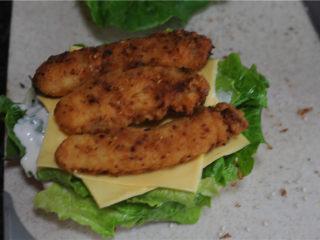 炸鸡芝士汉堡,摆上生菜叶,挤上沙拉酱,交替摆上两片芝士