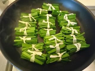 豆皮韭菜,扎好的韭菜豆皮,排進鍋裡慢火煎。