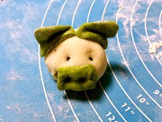 小猪豆沙包,取2个三角的绿色面皮蘸上小猪的耳朵