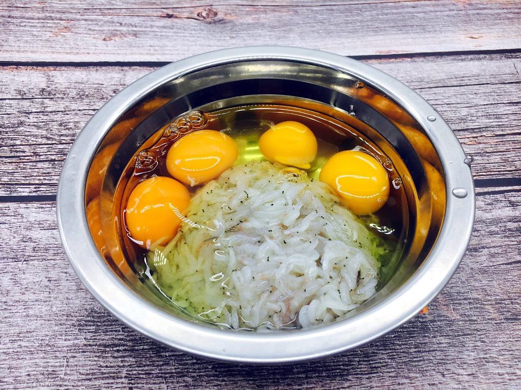 快手早餐 鲜虾皮鸡蛋饼,把鸡蛋磕入盛有鲜虾皮的容器里。</p> <p>